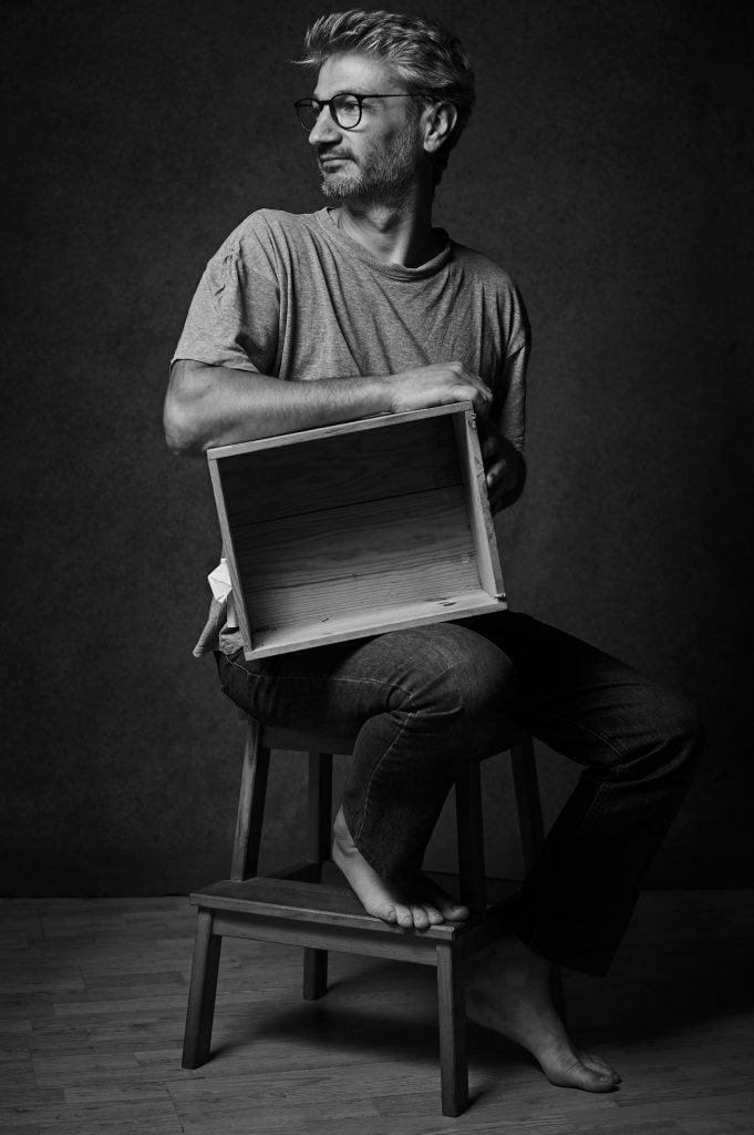 Autoportrait de Vincent Foret avec une caisse vide de vin.